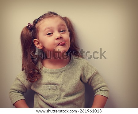 Fun smiling girl grimacing showing the tongue. Closeup vintage portrait - stock photo