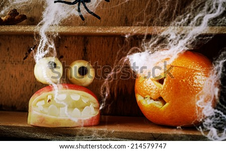 Fun spooky homemade Halloween food decorations with a carved apple mouth full of fearsome teeth topped with round dough eyes and a jack-o-lantern carved orange on a wooden shelf with spiders and webs - stock photo