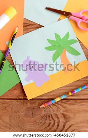Fun summer card with a hippopotamus and a palm tree on a wooden table. Preschool and kindergarten crafts. Materials for kids art. Paper and glue crafts activity for children. Early child development  - stock photo