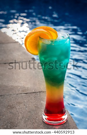 Fun summertime rum drink by the pool topped with orange slices - stock photo