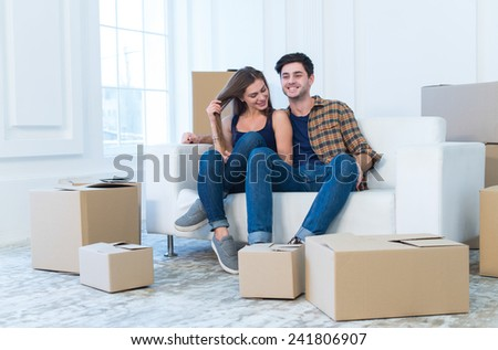 Fun while moving new flat. Young and beautiful couple is moving to new apartment surrounded with plenty of cardboard boxes. Both are smiling - stock photo