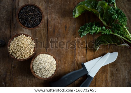 Fun with food, small wood bowls filled with brown rice, quinoa and wild rice on the left.  Kale, Swiss chard and porcelain knives on the right. Copy space dead center. This is shot on a wood table. - stock photo