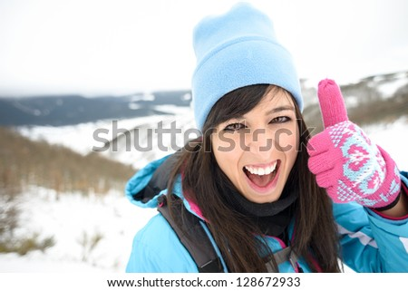 Fun woman hiking on winter mountain success with thumbs up. Female hiker achievement face expression outdoors. - stock photo