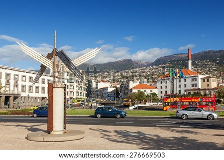 FUNCHAL, MADEIRA, PORTUGAL - NOVEMBER 3 2011: Sculpture standing at Autonomy Square with cars, touristic bus driving. With Funchal city at background. - stock photo