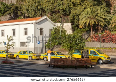 FUNCHAL, MADEIRA, PORTUGAL - NOVEMBER 3 2011: Taxi cars of various types waiting for clients on a street of Funchal city, Madeira island, Portugal - stock photo