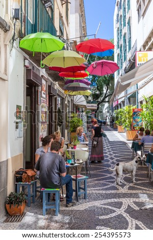 FUNCHAL, PORTUGAL - AUG 06: Tourists sitting at the terrace of a small restaurant in Funchal on August 06, 2014 at Funchal, capital city of Madeira, Portugal - stock photo