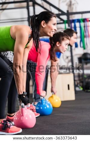Functional fitness workout in sport gym with kettlebell - stock photo