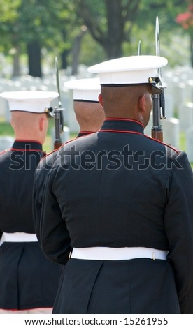 Funeral at Arlington National Cemetery with with military honor guard in foreground and gravestones in background - stock photo