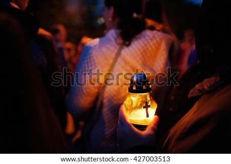 Funeral candle lamp in hand at night - stock photo