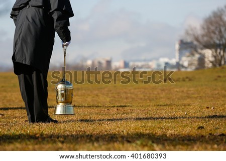 Funeral director, undertaker, starting to scatter ashes of a cremated human on a designated field for ash scattering. Death, cremation, funeral, Day of the dead concept.  - stock photo