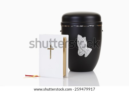 Funeral, urn with praying hands and white bible - stock photo
