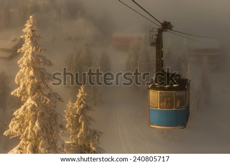 Funicular crossing over the snowy slope.Foggy atmosphere in winter season. - stock photo