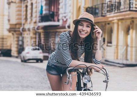 Funky beauty.  Beautiful young woman leaning at her bicycle and smiling while standing outdoors - stock photo