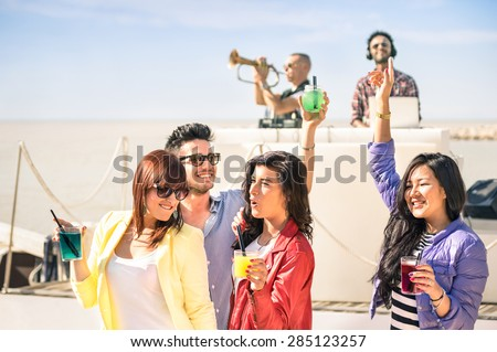 Funky people dancing music and having fun together at beach rave afterhour party - Deejay and trumpet player entertaining young happy friends - Dj playing trendy groove at summer open air disco club - stock photo