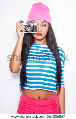 Funky photographer. Attractive young African woman in funky clothes focusing at you with her old-fashioned camera while standing against white background - stock photo