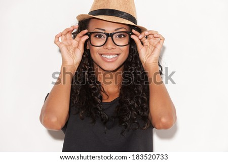Funky style beauty. Portrait of beautiful young African woman in glasses and funky hat adjusting her glasses and smiling while standing against white background - stock photo