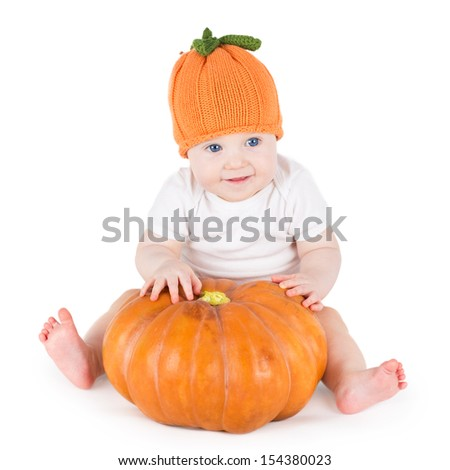 Funny adorable little baby playing with a big pumpkin wearing a knitted pumpkin hat on white background - stock photo