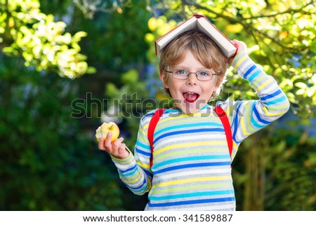 Funny adorable little kid boy with glasses, books, apple and backpack on his first day to school or nursery. Child outdoors on warm sunny day, Back to school concept - stock photo