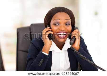 funny african american businesswoman talking on landline and mobile phone at same time - stock photo