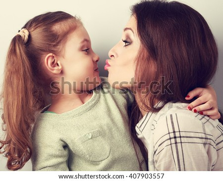 Funny amusing young mother wanting to kiss her comical grimacing daughter. Toned closeup portrait - stock photo