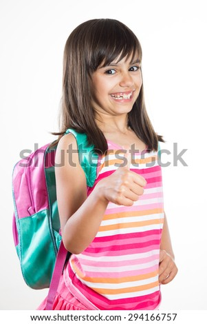 Funny and cheerful young school girl with schoolbag showing thumbs up. Isolated on white - stock photo