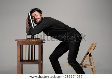 Funny and crazy man using a computer on gray background. human hands hug monitor. Concept of love to computer - stock photo