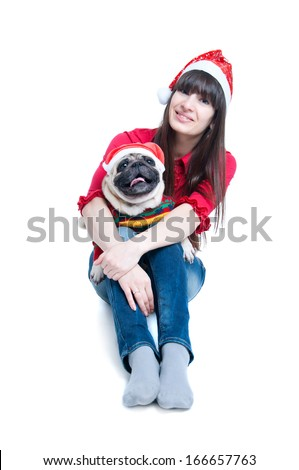 Funny and cute friends a pretty girl and her pug dog pet wearing red Santa Claus caps, having fun, smiling with toothy smiles, dog showing tongue, looking at camera. Isolated on white background - stock photo