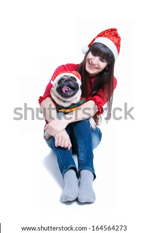 Funny and cute friends �¢?? pretty girl and her pug dog pet �¢?? wearing red Santa Claus caps, having fun, smiling with toothy smiles, dog showing tongue, looking at camera. Isolated on white background - stock photo