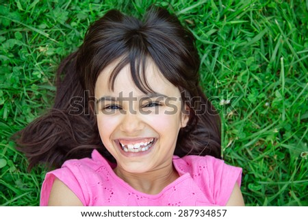 Funny and cute girl lying in the grass laughing showing irregular teeth - stock photo