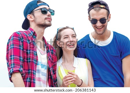 Funny and laughing guys in sunglasses go ahead. Young friends have fun together on the street and smile at each other. - stock photo