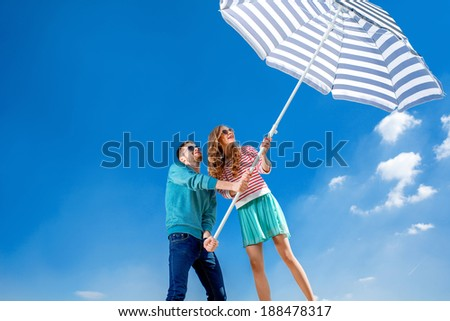 Funny and young couple have fun with beach umbrella on blue sky background - stock photo