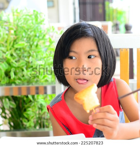 Funny Asian girl eating tasty bread with butter at table outdoor. - stock photo