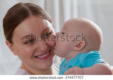 Funny baby boy kissing his mother indoors - stock photo