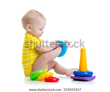 funny baby boy playing with colorful toy pyramid - stock photo
