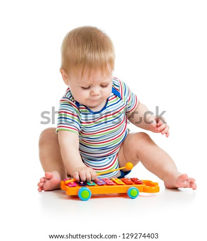 funny baby boy playing with musical toys - stock photo