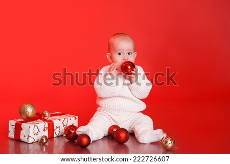 Funny baby boy sitting on floor with christmas presents and decorations over red background - stock photo
