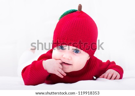 Funny baby girl in a red apple hat - stock photo