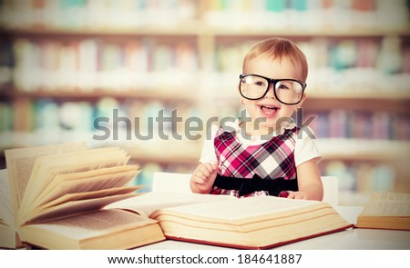 funny baby girl in glasses reading a book in a library - stock photo