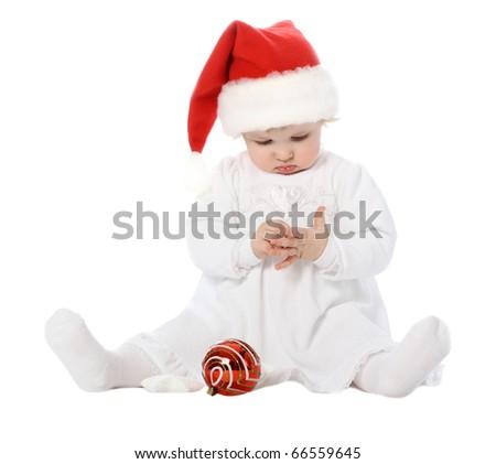 Funny baby girl in Santa's hat examining her fingers - stock photo