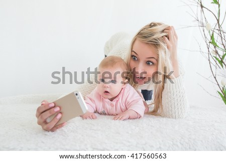 Funny baby girl make selfie on mobile phone and lying near her mother. Newborn looking at the camera and smiling.  - stock photo