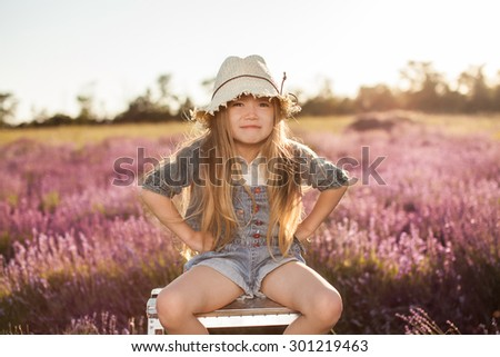 funny baby girl sitting on top stepladder outdoors - stock photo