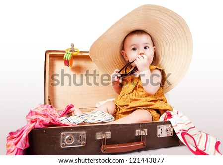 Funny baby in big summer hat girl sitting into old suitcase - stock photo