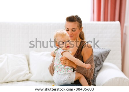 Funny baby sitting on mamas knees and looking back at home - stock photo