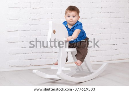 Funny baby sitting on the toy horse - stock photo