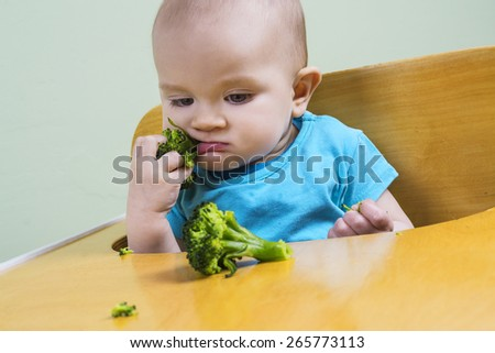 Funny baby tasting broccoli - stock photo
