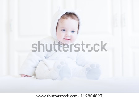 Funny baby wearing a teddy bear snow suit in a white bedroom - stock photo