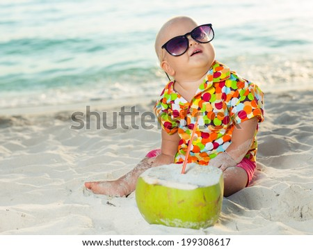 Funny baby wearing sunglasses with coconut - stock photo