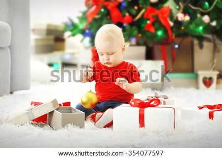 Funny baby with gift boxes and Christmas tree on background - stock photo