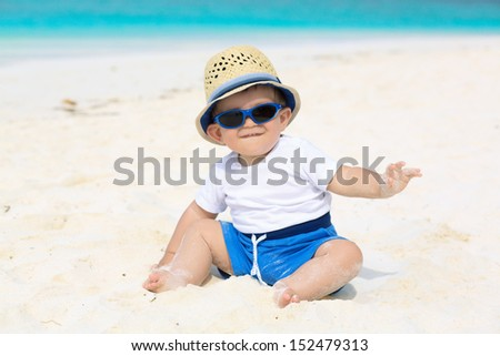 Funny baby with panama hat and sunglasses having tropical vacation - stock photo