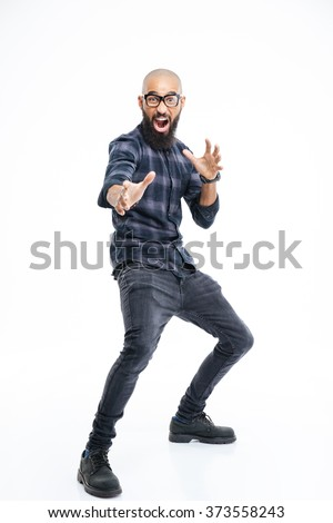 Funny baldheaded young african american man with beard standing and showing karate kick  - stock photo